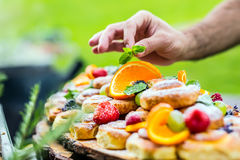 Chef Prepares A Plate Of Cakes With Fresh Fruits. He Is Working On The Herb Decoration. Outdoor Garden Party Stock Photo