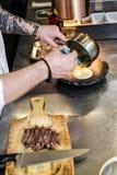 Chef prepares beef steak tenderloin in the restaurant kitchen. royalty free stock images