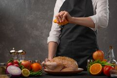 Chef prepares chicken for baking BBQ or oven. Pours orange juice. Against the background of vegetables and ingredients, with space