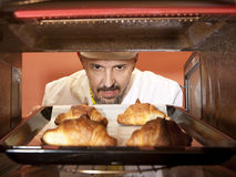 Chef prepares croissant in the oven Royalty Free Stock Images