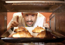 Chef prepares croissant in the oven Royalty Free Stock Image
