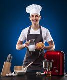 Chef prepares a delicious dish on a blue background. Studio photo stock images