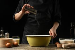 The chef prepares the dough for bread, pizza and sweets. The concept of food. On a black background, freezing in motion. Book of. Recipes, menus, cooking stock photo