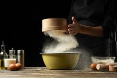 The chef prepares the dough for bread, pizza and sweets. The concept of food. On a black background, freezing in motion. Book of. Recipes, menus, cooking royalty free stock photos