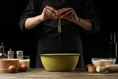 The chef prepares the dough for bread, pizza and sweets. The concept of food. On a black background, freezing in motion. Book of. Recipes, menus, cooking stock image