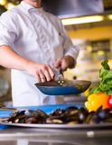 The Chef prepares food. Close up hands of chef frying dish, preparing food in the kitchen of a restaurant, cooking concept stock image
