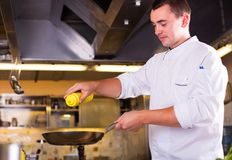 The Chef prepares food. Cooking food, profession and people concept - male chef frying dish at restaurant kitchen stock images
