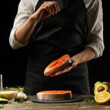 The chef prepares fresh salmon fish, Crumbu trout, sprinkles sea salt with ingredients. Preparing fish food. Salmon steak. Cooking. Vegan cuisine, restaurants stock photos