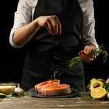 The chef prepares fresh salmon fish, freshly salted trout, sprinkled with rosemary leaves with ingredients. Salmon steak, royalty free stock images