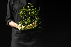 The chef prepares green beans, freezing. Black background for copying text. Cooking concept, cook books, recipes