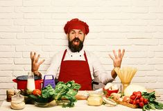 Chef prepares meal. Professional cookery concept. Cook with excited face. Sits by kitchen table with vegetables and kitchenware. Man with beard holds pretends stock photos