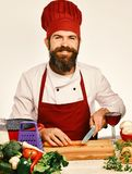 Chef prepares meal. Professional cookery concept. Man with beard cuts carrot with knife on white background. Cook with. Happy face in burgundy uniform sits by royalty free stock photo
