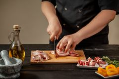 The chef prepares raw quail carcasses in the kitchen. Fresh raw meat quails ready for cooking on the wooden board. The chef prepares raw quail carcasses in the Royalty Free Stock Photography