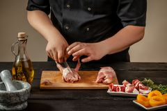 The chef prepares raw quail carcasses in the kitchen. Fresh raw meat quails ready for cooking on the wooden board. The chef prepares raw quail carcasses in the Stock Images