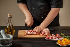 The chef prepares raw quail carcasses in the kitchen. Fresh raw meat quails ready for cooking on the wooden board. The chef prepares raw quail carcasses in the Stock Image