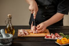 The chef prepares raw quail carcasses in the kitchen. Fresh raw meat quails ready for cooking on the wooden board. The chef prepares raw quail carcasses in the Royalty Free Stock Images