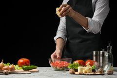 The chef prepares a salad, pours lemon juice on a dark background with an empty space for writing stock images