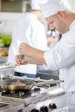 Chef prepares steak in pan at the kitchen Royalty Free Stock Photos