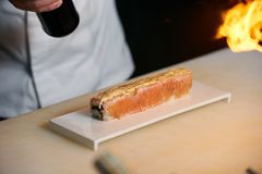 Chef prepares sushi with torch burner. Classic Japanese sushi food served on a stone plate royalty free stock images