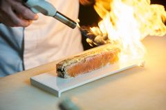 Chef prepares sushi with torch burner. Classic Japanese sushi food served on a stone plate stock image