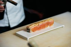 Chef prepares sushi with torch burner. Classic Japanese sushi food served on a stone plate stock photos