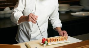 Chef prepares sushi with torch burner. Classic Japanese sushi food served on a stone plate stock images
