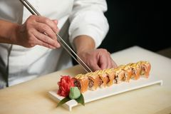 Chef prepares sushi with torch burner. Classic Japanese sushi food served on a stone plate royalty free stock image