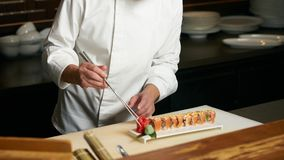 Chef prepares sushi with torch burner. Classic Japanese sushi food served on a stone plate royalty free stock photo