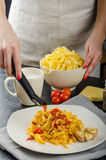 Chef prepares tagliatelle with garlic and cherry tomatoes Stock Images