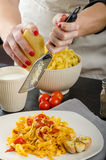 Chef prepares tagliatelle with garlic and cherry tomatoes Stock Image