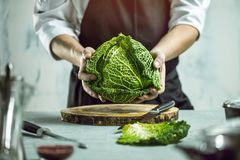 Chef prepares vegetables to cook in the restaurant kitchen. Chef cook preparing vegetables in his kitchen standing on the grey background holding a knife stock images
