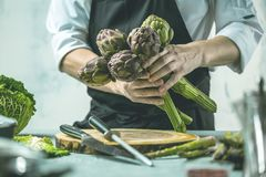 Chef prepares vegetables to cook in the restaurant kitchen. Chef cook preparing vegetables in his kitchen standing on the grey background holding a knife stock photo