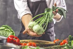 Chef prepares vegetables to cook in the restaurant kitchen. Chef cook preparing vegetables in his kitchen standing on the grey background holding a knife stock photography