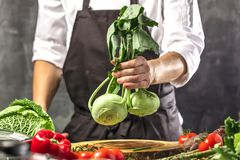 Chef prepares vegetables to cook in the restaurant kitchen. Chef cook preparing vegetables in his kitchen standing on the grey background holding a knife royalty free stock photos