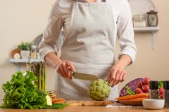Chef preparing artichoke. The concept of losing healthy and wholesome food, detox, vegan eating, diet, cooking. Slow food, comfort royalty free stock photography