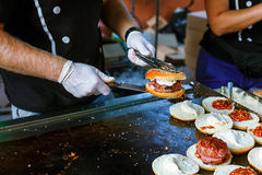 Chef preparing burgers at the barbecue outdoors Stock Photos