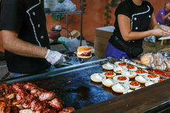 Chef preparing burgers at the barbecue outdoors Stock Image