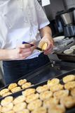 Chef preparing desserts removing them from. Individual ramekins or moulds and placing them out on a tray in a commercial kitchen Stock Images