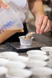 Chef preparing desserts removing them from moulds. Chef preparing desserts removing them from individual ramekins or moulds and placing them out on a tray in a Royalty Free Stock Photo