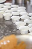 Chef preparing desserts removing them from moulds. Chef preparing desserts removing them from individual ramekins or moulds and placing them out on a tray in a Royalty Free Stock Images