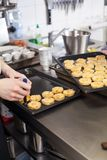 Chef preparing desserts removing them from moulds. Chef preparing desserts removing them from individual ramekins or moulds and placing them out on a tray in a Royalty Free Stock Photography