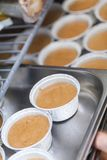 Chef preparing desserts removing them from moulds. Chef preparing desserts removing them from individual ramekins or moulds and placing them out on a tray in a Stock Photography