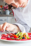 Chef preparing dish with bersaola and mixed salad Royalty Free Stock Photos