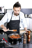 Chef preparing dishes in a frying pan Royalty Free Stock Photo
