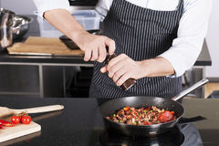 Chef preparing dishes in a frying pan Stock Photography