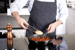 Chef preparing dishes in a frying pan Royalty Free Stock Photos