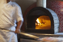 Chef cooking pizza. In a traditional oven in a restaurant kitchen Royalty Free Stock Photos
