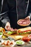 Chef preparing fresh baguette sandwiches stock image