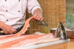 Chef preparing a fresh salmon fish on a cutting board, Japanese chef. Stock Photo