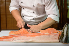 Chef preparing a fresh salmon fish on a cutting board, Japanese chef Stock Images